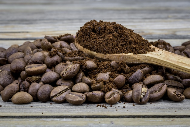 Fragrant coffee beans in a beautiful wooden spoon on wood