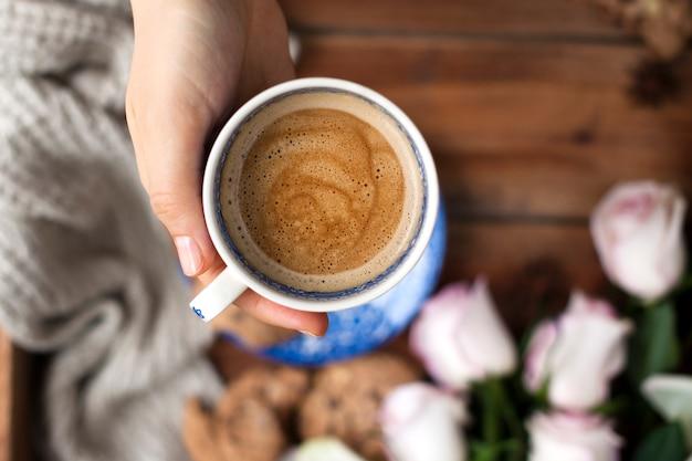 여자의 손에 향기로운 커피, 흰 장미 꽃다발과 가을의 아늑함. 좋은 아침. 상단보기. spase를 복사하십시오.