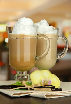 Fragrant coffee latte in glasses cups with vanilla pods, on table in cafe