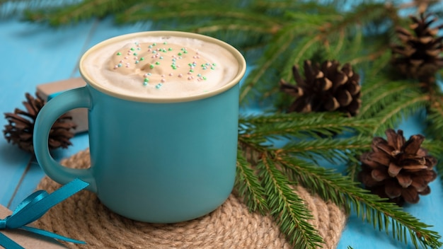 Fragrant delicious coffee on a light blue table with fir branches and cones