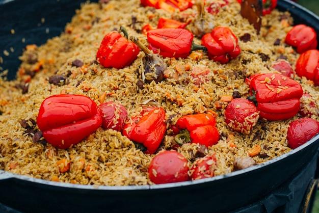 Ароматный вкусный плов с чесноком и большим болгарским перцем. уличная праздничная свежеприготовленная еда.