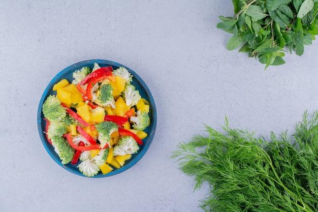 Aneto fragrante e fasci di menta accanto a un piatto di insalata su sfondo marmo. foto di alta qualità