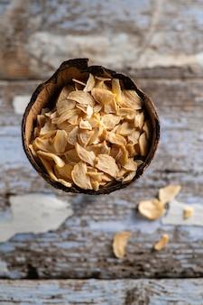 古い木製の背景、クローズ アップ、トップ ビューでココナッツ ボウルにフレークで香りのよい乾燥ニンニク