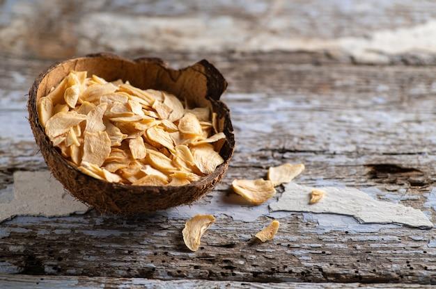 古い木製の背景にココナッツ ボウルのフレークで香りのよい乾燥ニンニク、上面図、テキスト用の空きスペース