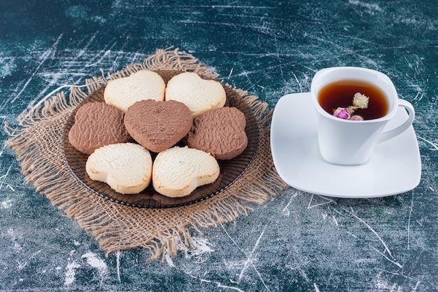 Ароматное свежее печенье в форме сердца и чашка травяного чая на деревянной доске.