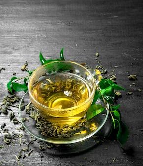 Fragrant green tea with leaves on black chalkboard
