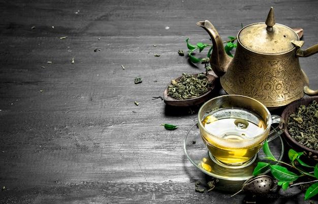 黒い黒板に葉が付いた香りのよい緑茶