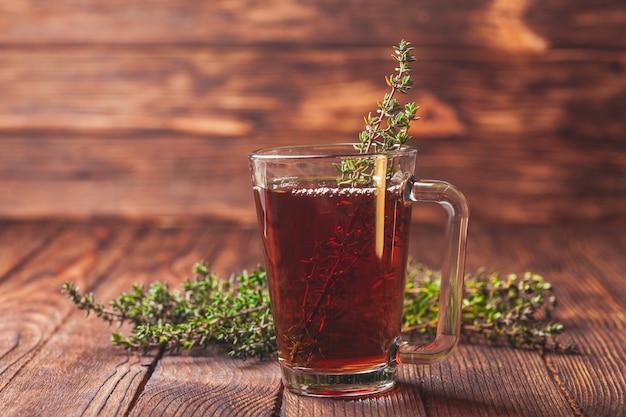Ароматный травяной чай с пучками тимьяна в стеклянной кружке
