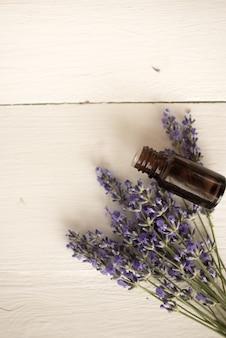 ラベンダーオイルの香りのよい瓶と野生の花の繊細な花束。健康的な睡眠のための薬。