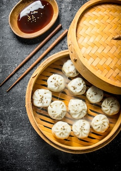 Fragrant manta dumplings in a bamboo steamer with soy sauce in a plate. on rustic