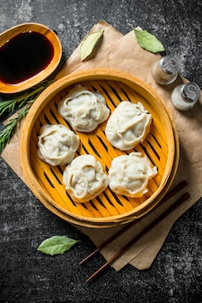 Fragrant manta dumplings with spices and soy sauce. on dark rustic