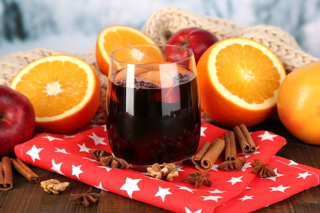 Fragrant mulled wine in glass on napkin on winter surface