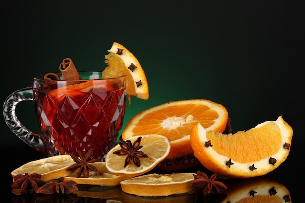 Fragrant mulled wine in glass with spices and oranges around on green