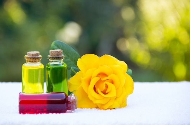 Fragrant natural flower oils in small bottles and yellow rose