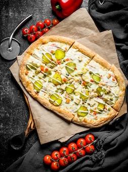 Ароматная пицца с овощами и помидорами на ветке. на деревенском фоне