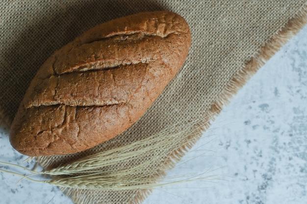 Fragrant rye bread on stone background.