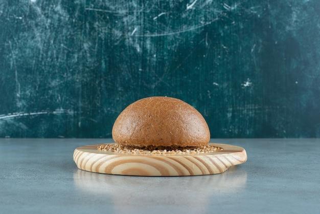 Ароматная ржаная булочка на деревянной тарелке с ячменем.