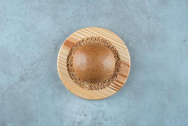 Panino di segale fragrante su piatto di legno con orzo.