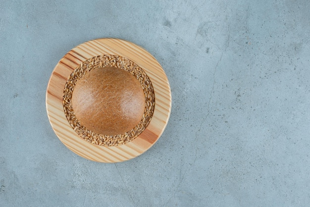 Fragrant rye bun on wooden plate with barley.