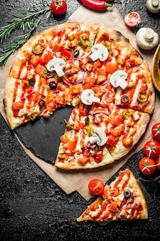 버섯과 토마토를 곁들인 향기로운 슬라이스 멕시코 피자. 검은 소박한 배경에