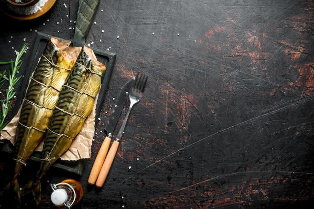 Скумбрия ароматная копченая на разделочной доске. на темном деревенском столе