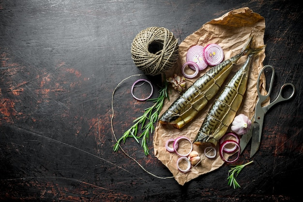 Fragrant smoked mackerel on paper with twine and chopped onion. on dark rustic background