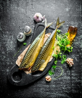 Fragrant smoked mackerel with herbs and garlic cloves. on dark rustic background
