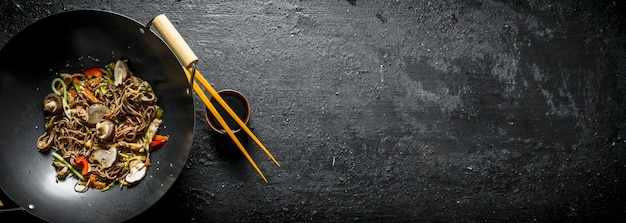 Fragrant soba noodles in a wok pan. on black rustic table