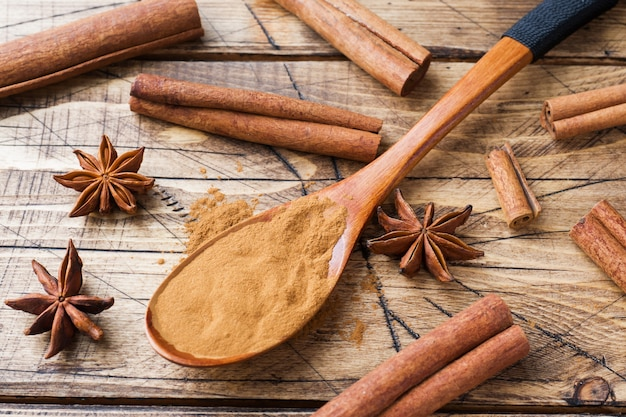 Fragrant spices cinnamon sticks and ground, star anise on wooden background.