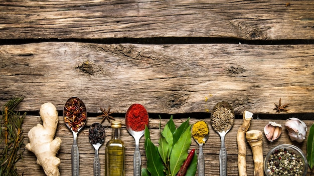 Fragrant spices in spoons with herbs, garlic and olive oil. on wooden background. free space for text . top view