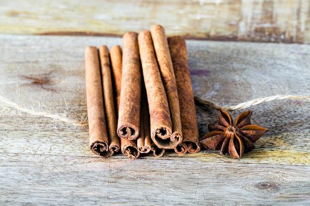 乾燥した香りのよいスターアニスと一緒にテーブルクロスに樹皮シナモンの香りのよいスティック、キッチンの領域でおいしいオリエンタルスパイスのクローズアップ