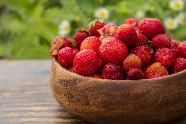 Fragrant strawberry in a wooden plate on a table in the garden. copy space