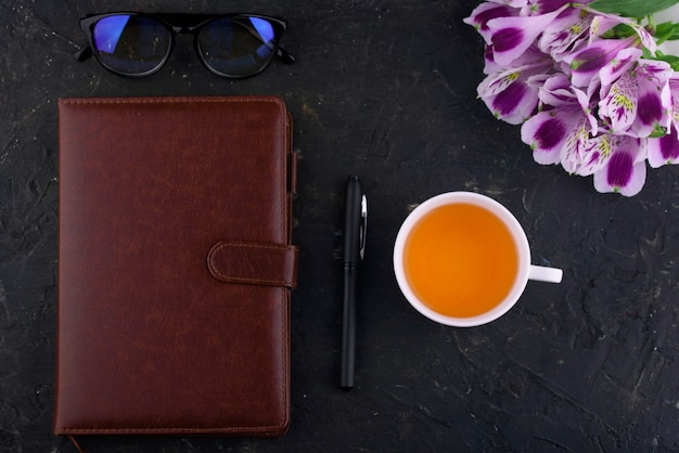 Fragrant tea in a white cup, beautiful flowers, a notebook with a pen and glasses.