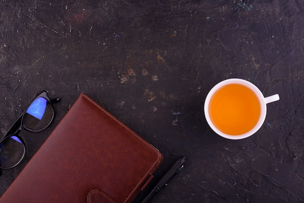 Fragrant tea in a white cup, a notebook with a pen and glasses.