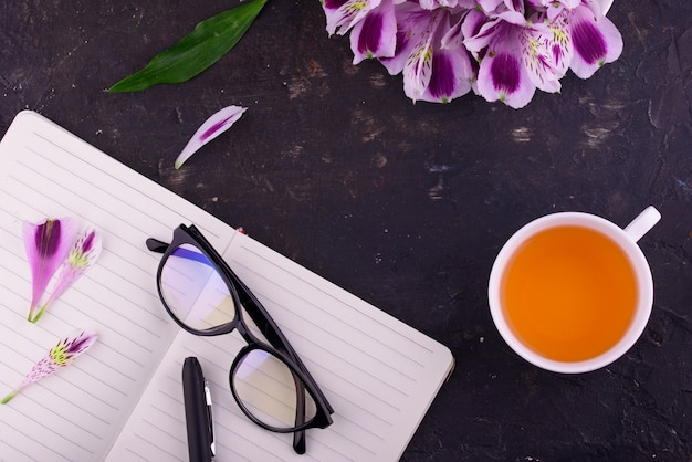 Fragrant tea in a white cup with a notebook and glasses on a black