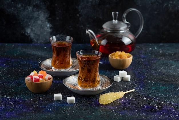 Tè profumato con caramelle sulla superficie blu