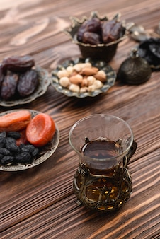 Fragrant turkish tea with dried fruits; nuts and dates on textured wooden desk