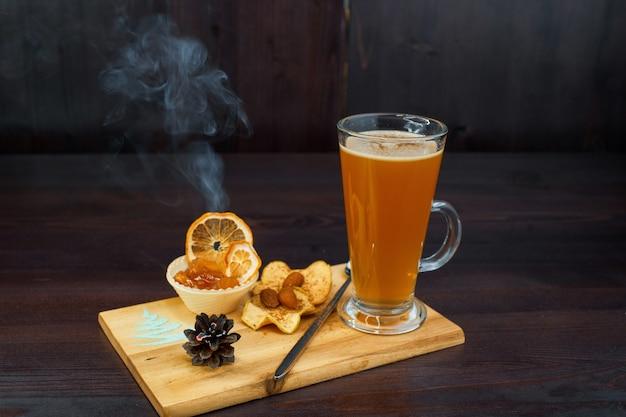 カフェの木の板の上に、生姜などの効いた食材を使った黄金色の香り高い温かい飲み物が立っています。アプリコットジャムとドライフルーツを添えたドリンク