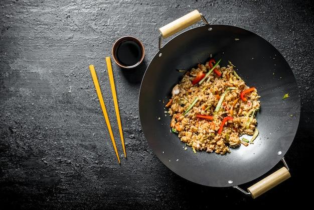 닭고기와 야채를 곁들인 향긋한 웍 라이스. 어두운 시골 풍 테이블에