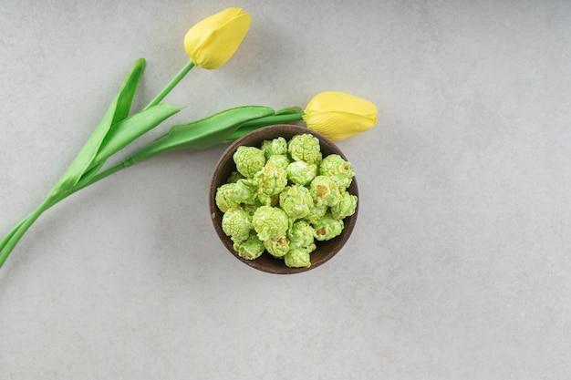 大理石のポップコーンキャンディーのボウルの隣に置かれた香りのよい黄色いチューリップ。