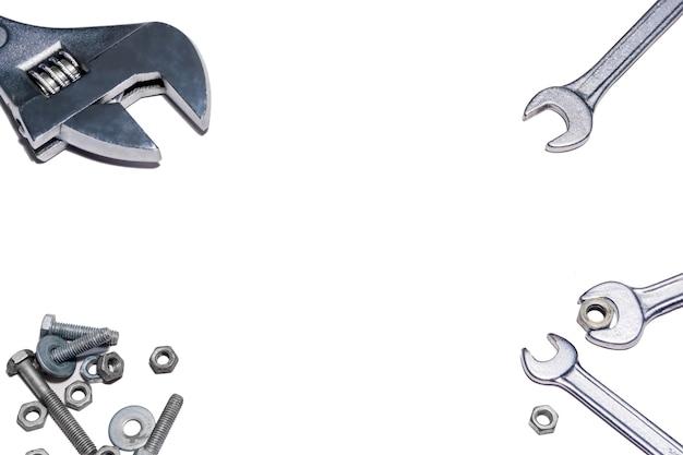 프레임 - 조정 가능한 스패너 및 일반 렌치, 너트 및 볼트는 흰색 배경에 있습니다.
