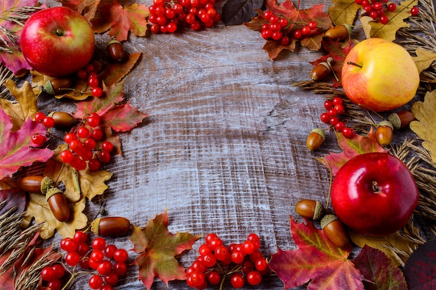 Frame of apples, acorns, berries and fall leaves on the rustic wooden