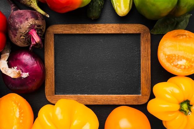 暗い背景に野菜で作られたフレームの配置