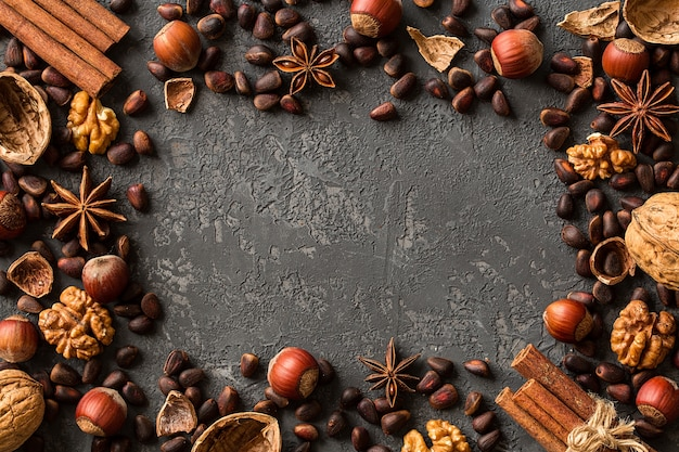 Frame of assorted nuts over  dark concrete