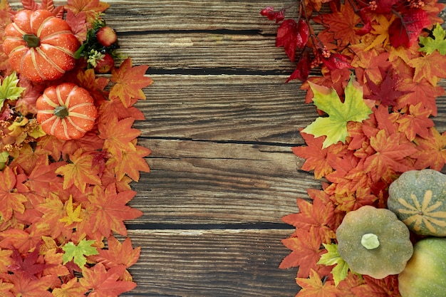 Frame of autumn leaves and pumpkins old wooden background with copy space
