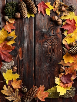 Frame of autumn leaves on wooden background with copy space.