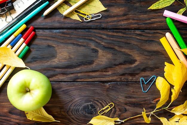 Рамка снова в школу стол с осенними листьями, яблоком и школьными принадлежностями вид сверху плоская планировка
