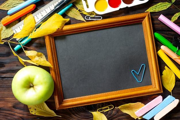 Рамка снова в школу стол с осенними листьями, яблоком и школьными принадлежностями вид сверху