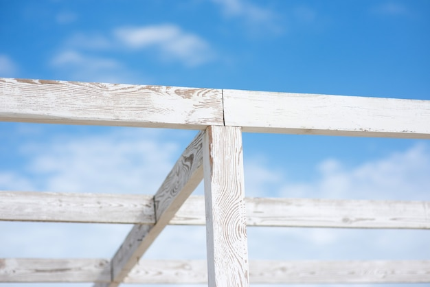 Frame of a beach canopy made of wooden slats, against a background of blue sky
