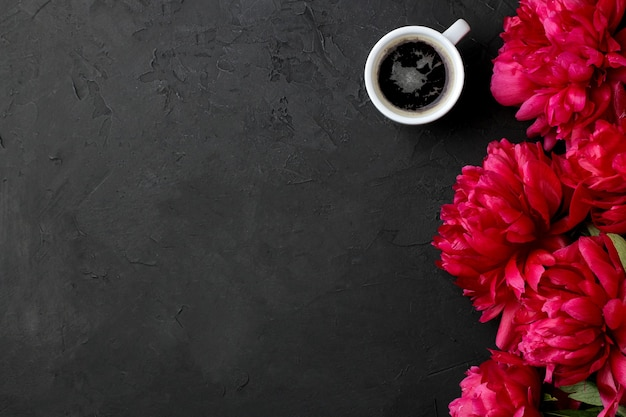 Frame of beautiful bright pink flowers peonies and a cup of coffee on a black graphite background. top view. space for text
